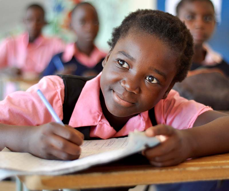 Girl writing in a Zambian school partnered with Beyond Ourselves