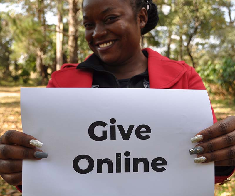 Zambian school teacher holding sign that reads: 'Give Online'