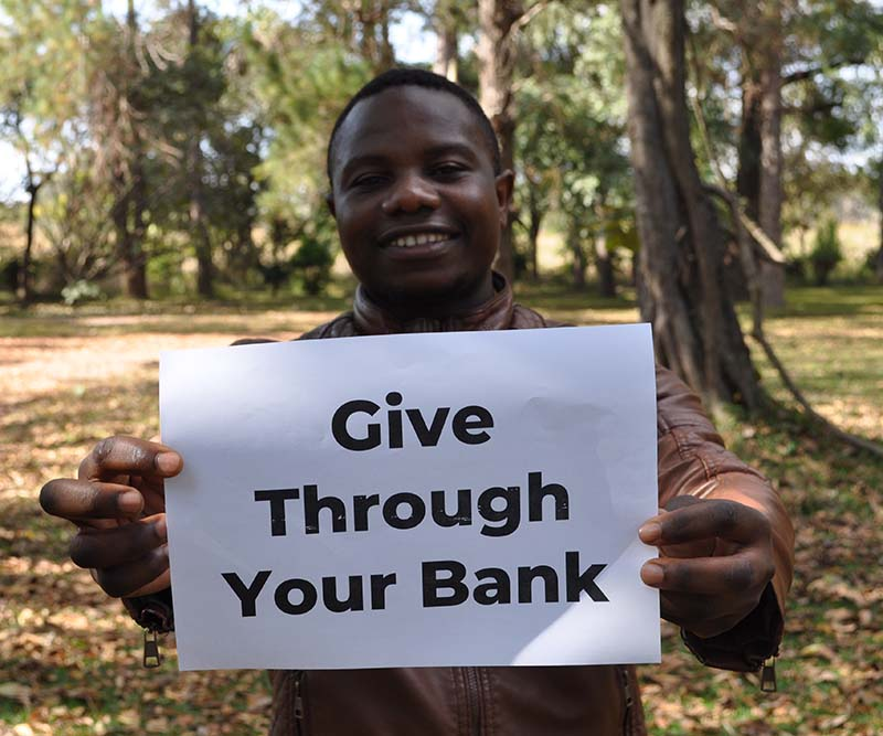 Zambian school teacher holding sign that reads: 'Give Through Your Bank'