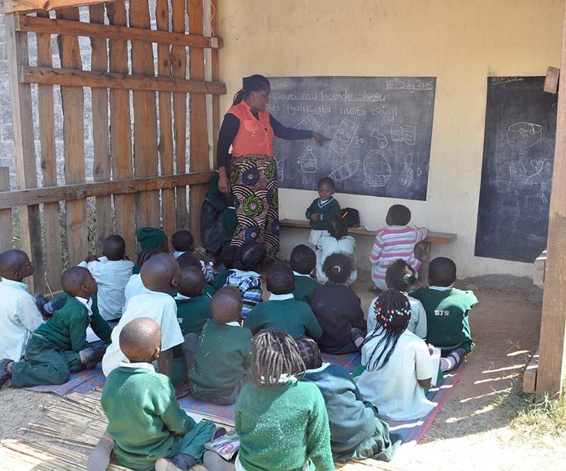 Zambian teaching young children from a blackboard