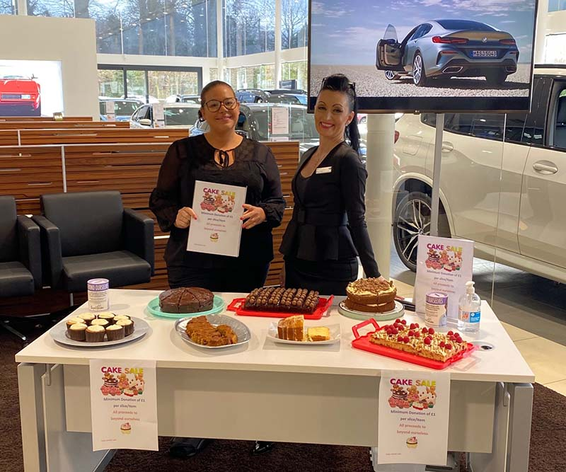 Two Stephen James BMW employees getting involved by running a cake sale to fundraise for Beyond Ourselves