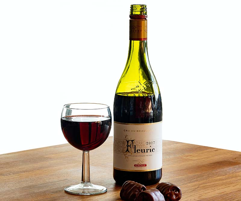 Bottle of red wine with a glass and some chocolates